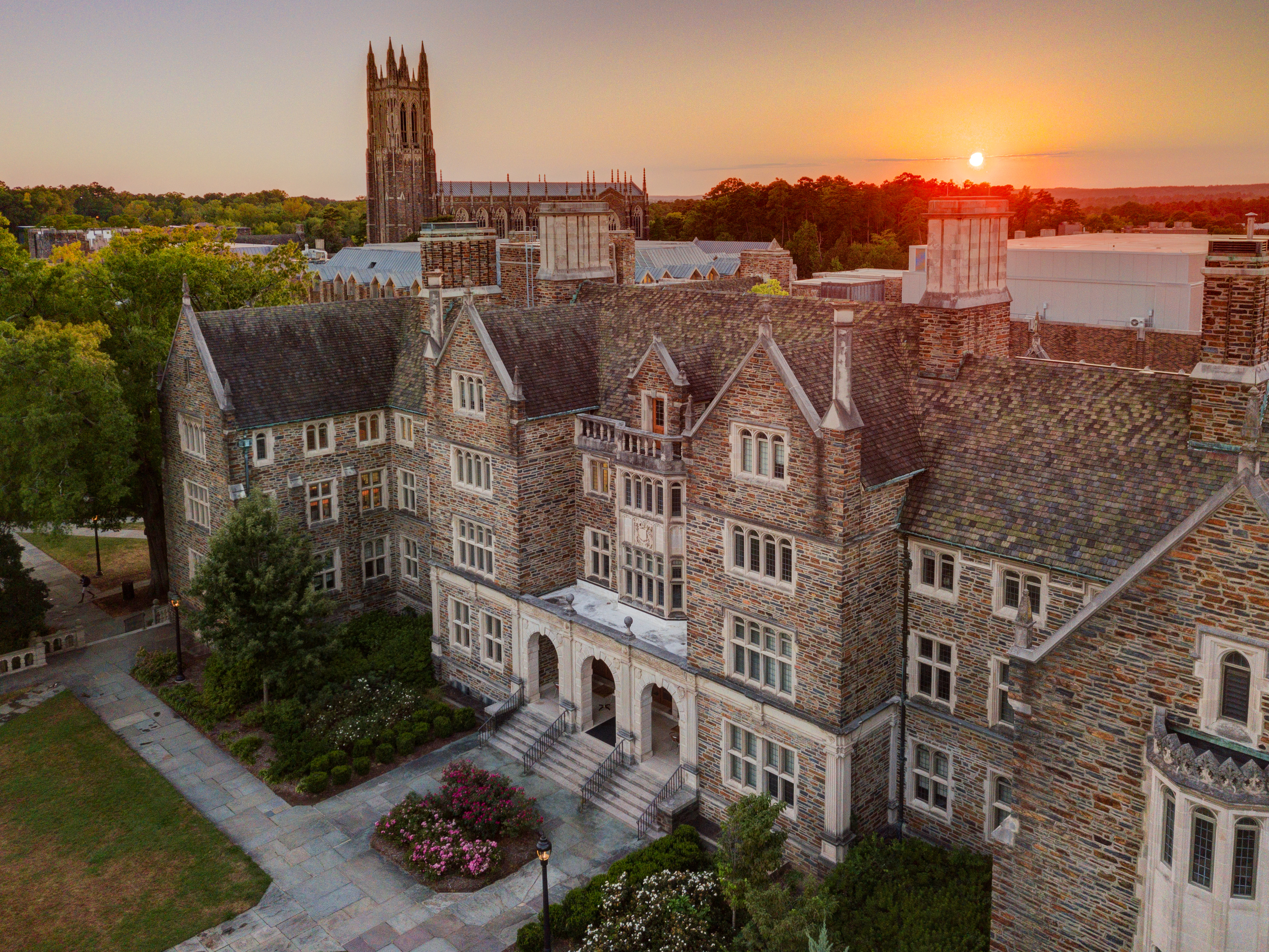 A picture of the sun setting over the Duke University chapel and other buildings on campus.